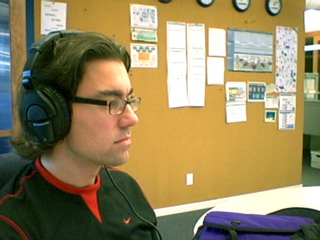 [Derek wears big Sennheiser headphones at work