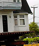 [Closeup of house raised for moving]
