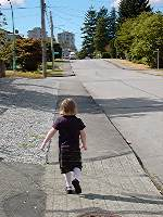 [Girl walking away up a suburban street]